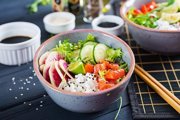 Hawaiian salmon fish poke bowl with rice, cucumber, radish, sesame seeds and lime.