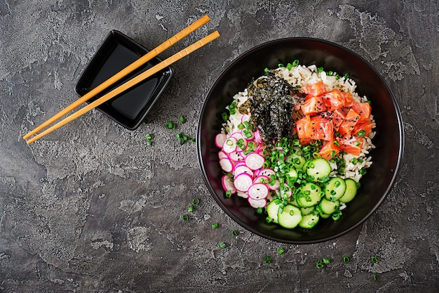 Hawaiian salmon fish poke bowl with rice, radish,cucumber, tomato, sesame seeds and seaweeds. buddha bowl. diet food. top view. flat lay