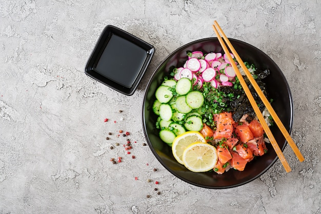 Hawaiian salmon fish poke bowl with rice, radish,cucumber, tomato, sesame seeds and seaweeds. buddha bowl. diet food. top view. flat lay