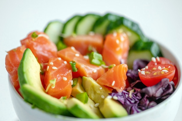 Hawaiian salmon poke bowl with cucumber, tomato, sesame seeds, avocado.