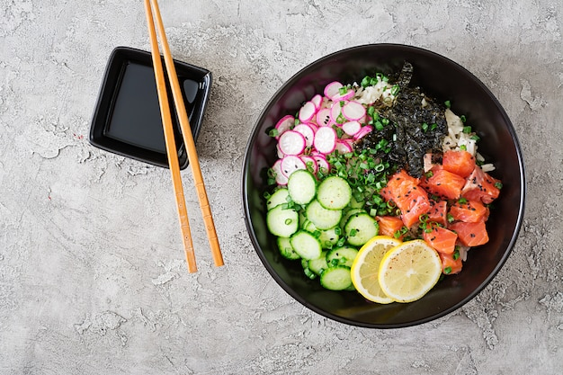 Hawaiian salmon poke bowl with rice, radish,cucumber, tomato, sesame seeds and seaweeds