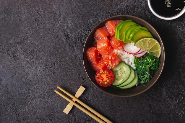 Салат из гавайского лосося с рисом, овощами и водорослями подается в миске.