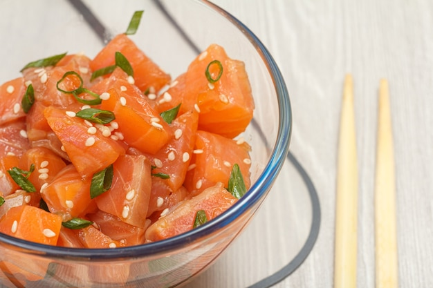 Hawaiian salmon poke with green onions and sesame seeds in glass bowl with chopsticks