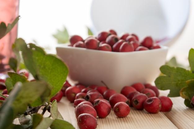 木製のテーブルの上の白いボウルにサンザシの果実