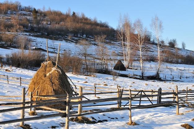Haystacks and a fence of wood, winter landscape, rural life, rest in the mountains in the village