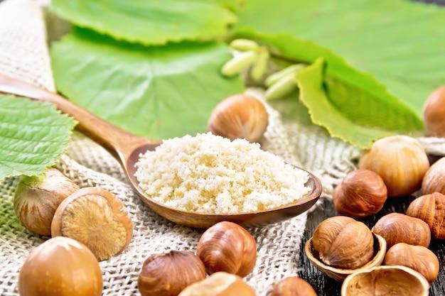 スプーンのヘーゼルナッツ粉と解任のナッツ、木の板の背景に緑の葉を持つヘーゼルナッツの枝