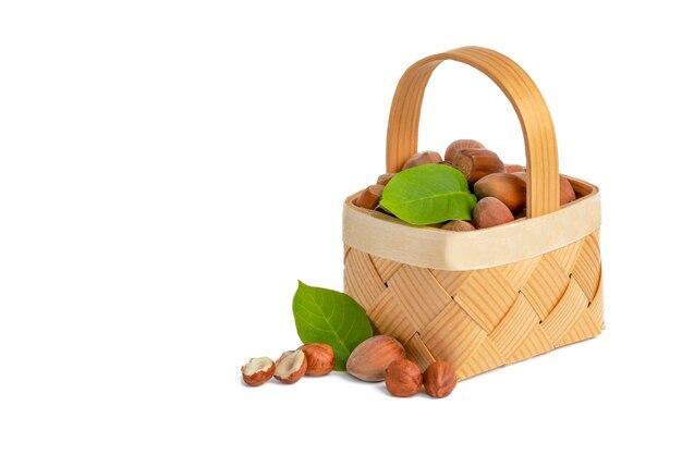 헤이즐넛은 껍질과 초에 껍질을 벗기지 않은 헤이즐넛이 분리된 흰색 배경에 있는 나무 바구니에 있습니다.