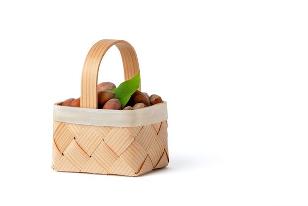 헤이즐넛은 격리된 흰색 배경에 있는 나무 바구니에 있습니다. 껍질과 녹색 잎에 껍질을 벗기지 않은 헤이즐넛.
