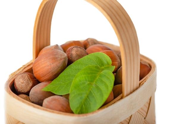 헤이즐넛은 격리된 흰색 배경에 있는 나무 바구니에 있습니다. 껍질을 벗기지 않은 헤이즐넛과 녹색 잎