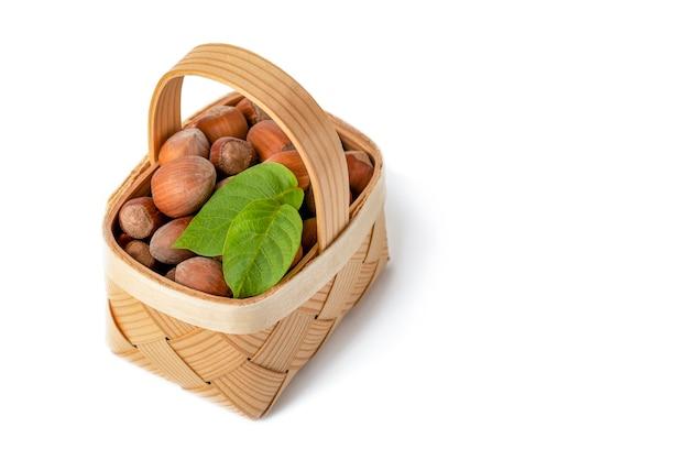 헤이즐넛은 흰색 격리된 배경에 있는 나무 바구니에 있습니다. 껍질을 벗기지 않은 헤이즐넛과 녹색 잎