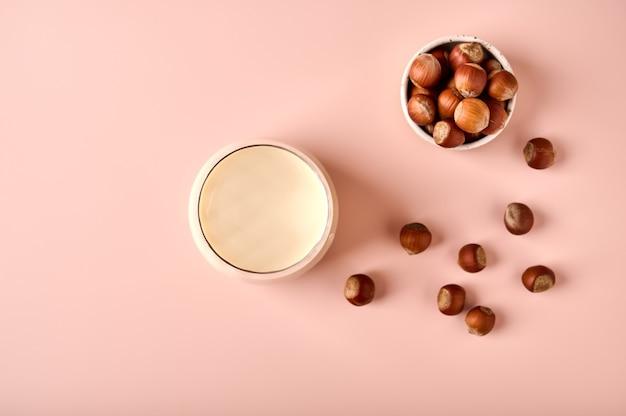 ガラスのヘーゼルナッツミルクとピンクの粉の背景の上のナッツの種