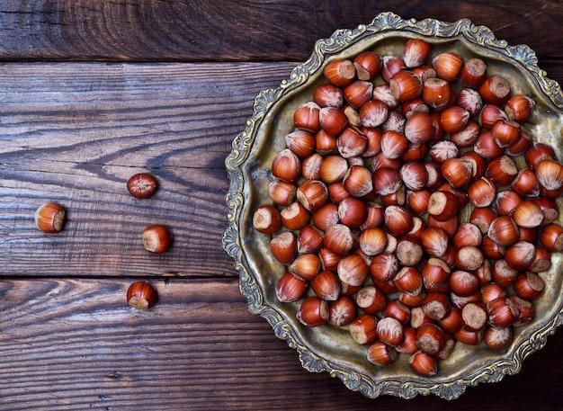 Hazelnut nut in shell on an iron copper plate