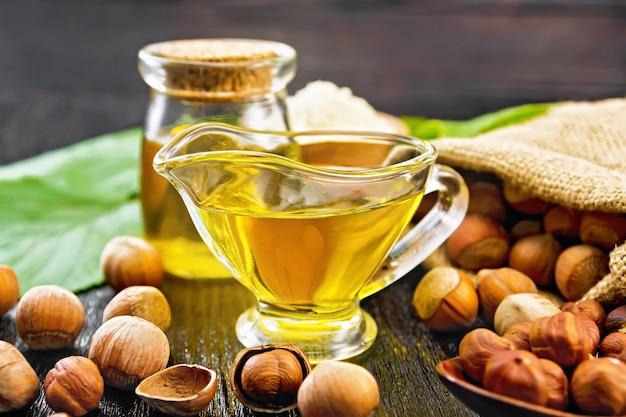 ガラスの瓶とグレイビーボートのヘーゼルナッツオイル、ボウルの小麦粉、バッグ、スプーン、テーブルの上のナッツ、暗い木の板の背景に緑の葉とヘーゼルナッツの小枝