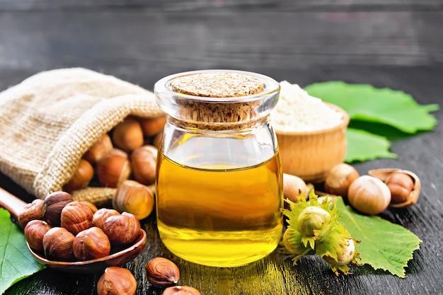 ガラスの瓶にヘーゼルナッツオイル、ボウルに小麦粉、バッグ、スプーン、テーブルにナッツ、木の板の背景に緑の葉とヘーゼルナッツの小枝