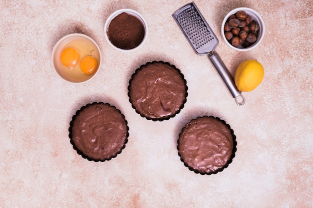Hazelnut; whole lemon; cocoa powder; hand grater and egg yolk on textured backdrop