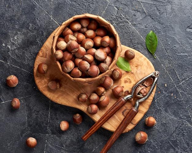 オリーブの木の板にくるみ割り人形とヘーゼルナッツ。緑の葉とナッツ。上面図。