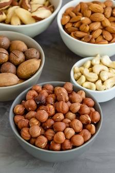 Hazelnuts, almonds, brazilian nuts, cashews, macadamia, pecans and pistachios in bowls on a dark concrete background.