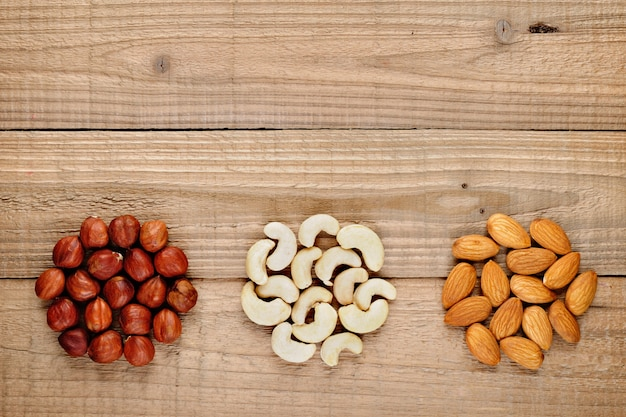 Hazelnuts, almonds and cashew nuts on wood