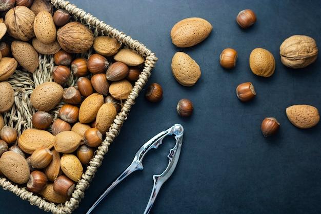 Фундук, миндаль, грецкие орехи в корзине на темном фоне.