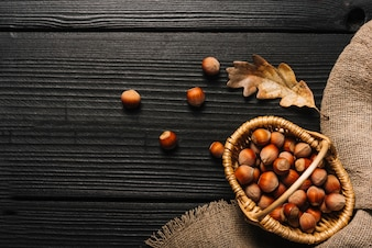 Hazelnuts and dried leaf near cloth