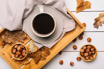 Hazelnuts and leaves near tray with coffee
