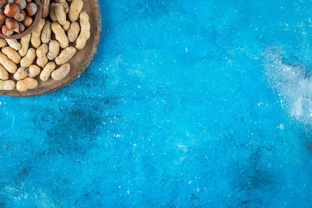Nocciole in una ciotola a bordo con arachidi sulla superficie blu