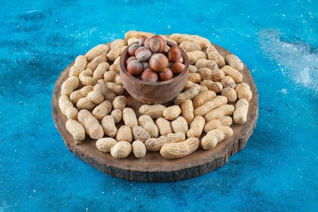 Nocciole in una ciotola a bordo con arachidi, sul tavolo blu.