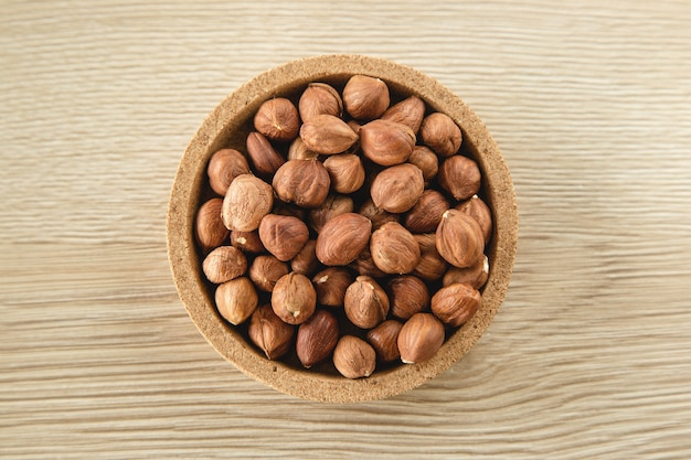 Hazelnuts in the bowl on wooden background, concept of healthy eating vegan food. top view, selective focus, copy space