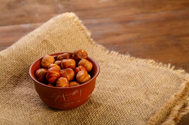 Hazelnuts in a clay cup on burlap on a wooden table.