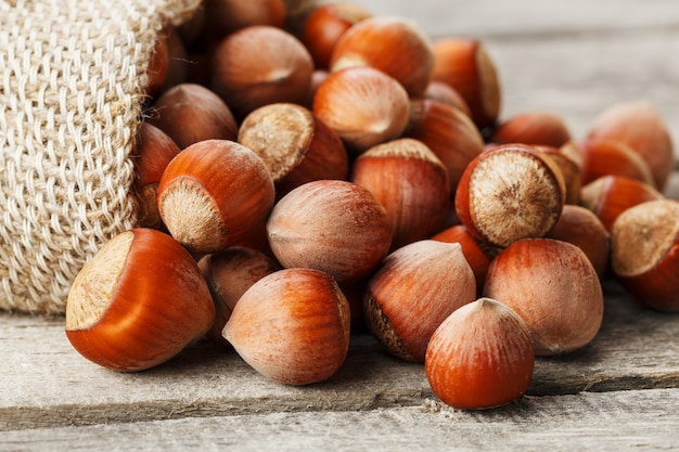 Hazelnuts in a cover, poured out from a bag from burlap on a gray wooden table