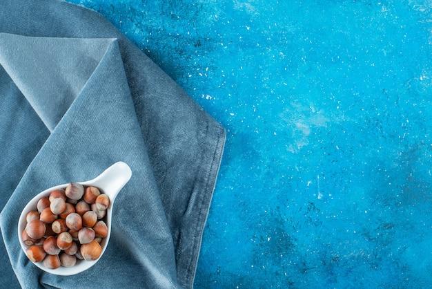 파란색 표면에 직물 조각에 숟가락에 헤이즐넛