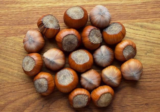 木製の背景にヘーゼルナッツ。殻付きヘーゼルナッツ、健康食品
