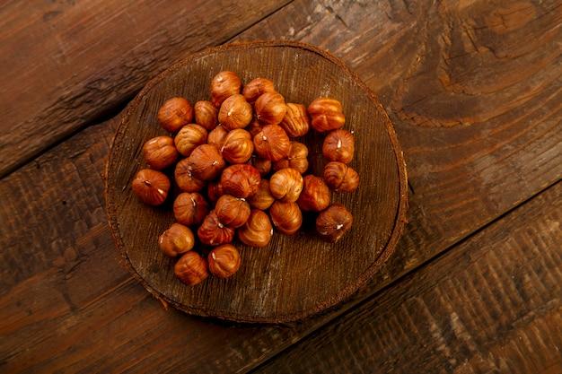 木製の丸い板に散らばったヘーゼルナッツ