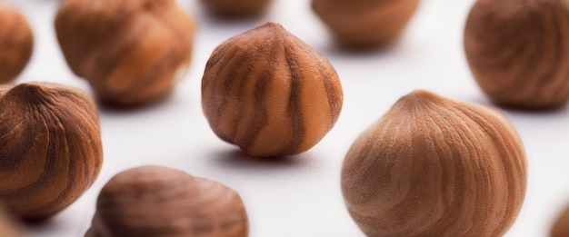 Hazelnuts scattered on a white wall, whole, selective focus. the concept of healthy eating.