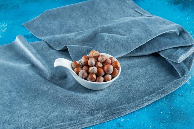 Nocciole in un cucchiaio su un pezzo di tessuto, sul tavolo blu.