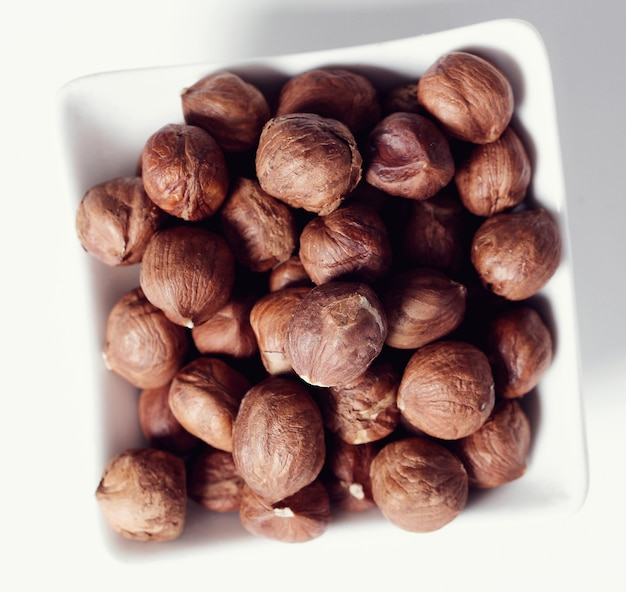 Hazelnuts on white bowl