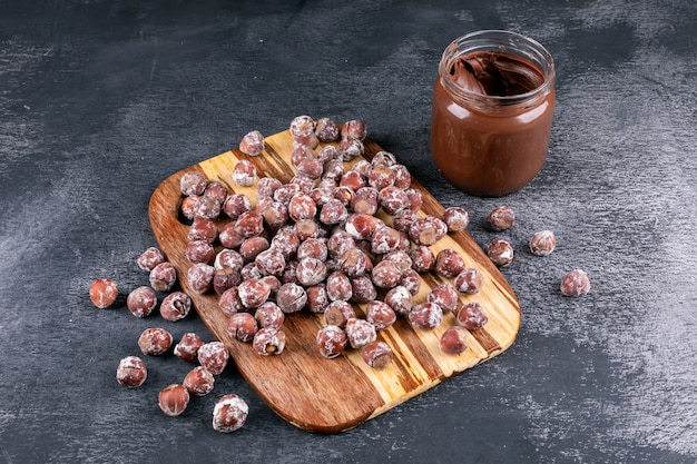 Hazelnuts with cocoa spread high angle view on a wooden cutting board and dark stone table