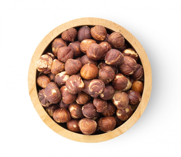 Hazelnuts in wood bowl  isolated on white