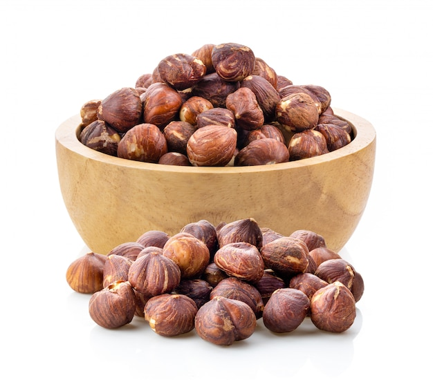 Hazelnuts in wood bowl  on white