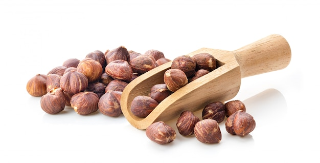 Hazelnuts in wood scoop  on white