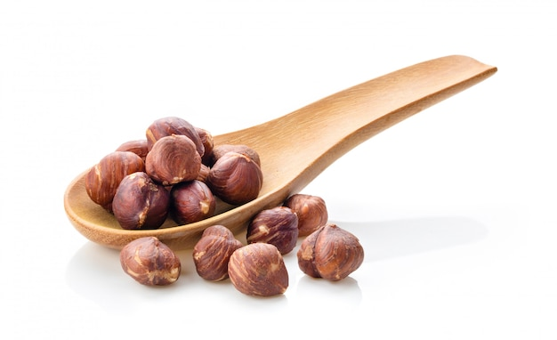 Hazelnuts in wood spoon on white