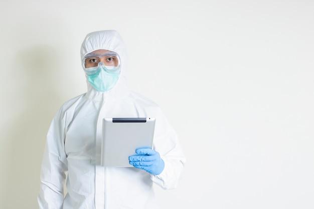 Человек носить костюм hazmat с помощью планшета читать информацию о вспышке заразной болезни covid19 копией пространства