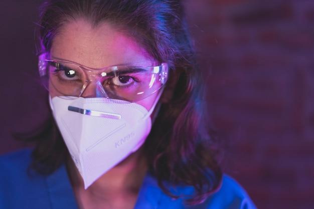 Медсестра в костюме hazmat, защитных очках и противовирусной маске kn95 для covid19