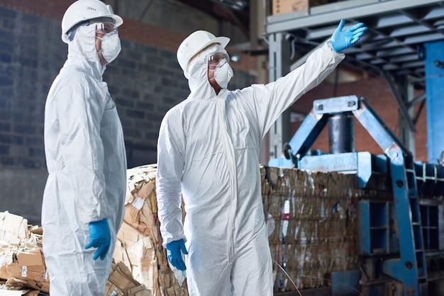Рабочие в костюмах hazmat на современной фабрике