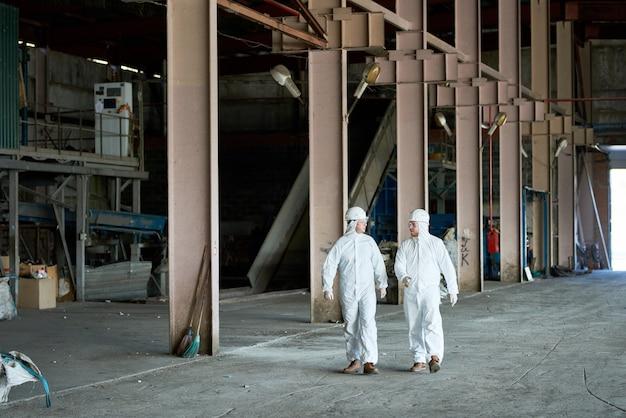 Рабочие, носящие костюмы hazmat на фабрике