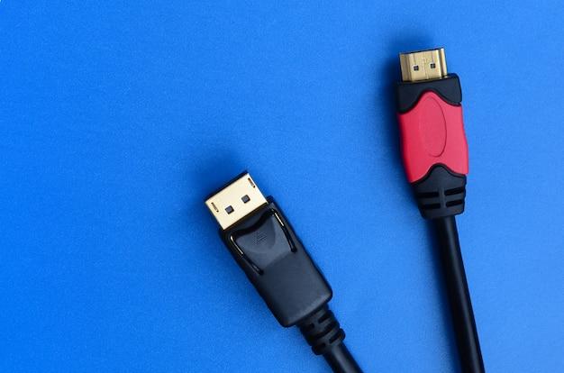 Аудио-видео hdmi-штекер компьютерного кабеля и 20-контактный штекер позолоченного разъема displayport для безупречного соединения на синем фоне