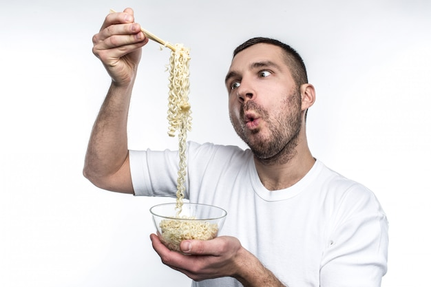 He adores to eat every junk food in a world. especially he likes to eat food from oriental cuisine. young man can't wait to eat it. isolated on white wall.