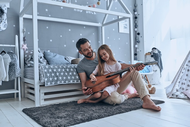 He always believes in her. young father teaching his little daughter to play guitar and smiling