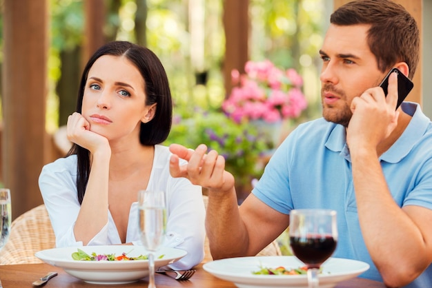 Он всегда меня игнорирует. подавленная молодая женщина, взявшись за подбородок и глядя в камеру, пока ее парень разговаривает по мобильному телефону в ресторане на открытом воздухе