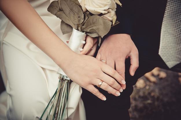 彼と彼女は手をつないでいます。結婚指輪とブーケ